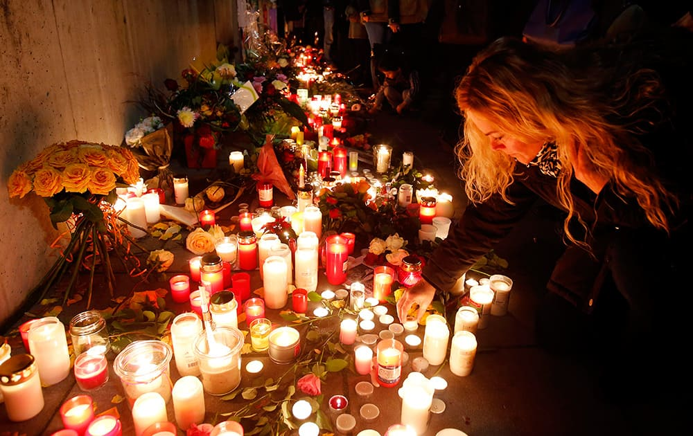 A woman lights a candle in front of a hospital in Offenbach, Germany, to commemorate 23-year old Tugce A. who was beaten up two weeks ago in front of a fast food branch when she tried to help two other girls.