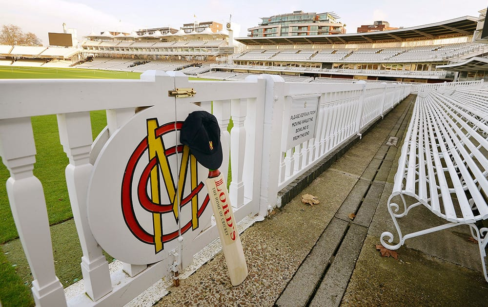 A cricket bat and cap rest against the boundary fence at Lord's Cricket Ground, the home of modern cricket, in London, in memory of Phillip Hughes, who died after injuries suffered when he was struck on the head by a bouncer at the Sydney Cricket Ground.