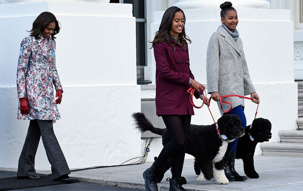 First lady Michelle Obama, left, follows her daughters Malia Obama, center, and Sasha Obama, as they arrive to welcome the Official White House Christmas Tree to the White House in Washington.