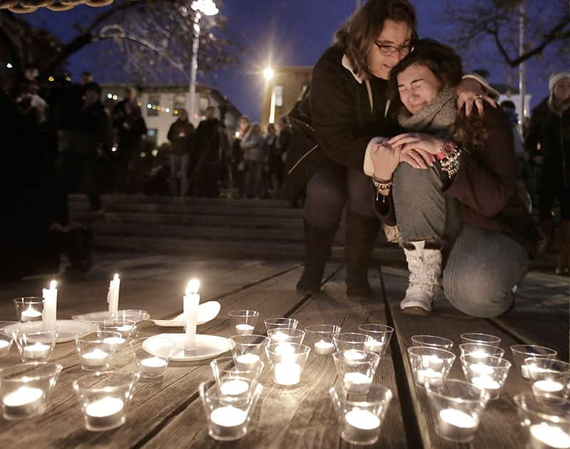 After leaving a candle at the edge of the Manayunk Canal, a woman is comforted by another during a candlelight vigil, for Shane Montgomery, at a park across from Kildare's Irish Pub in the Manayunk section of Philadelphia, Pa.