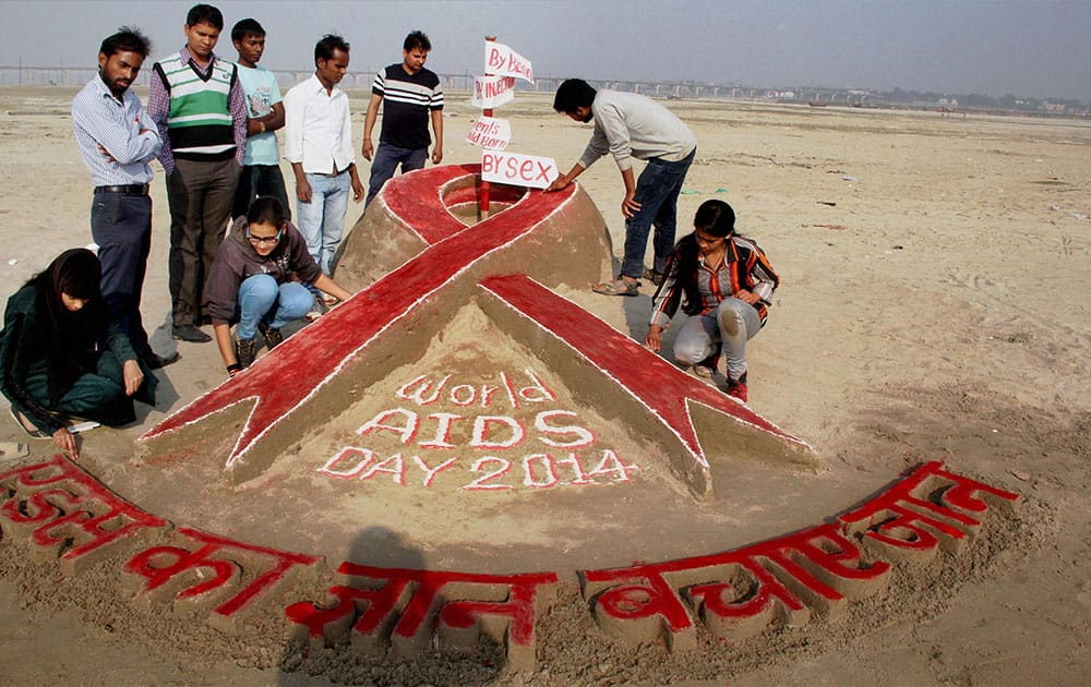 Students of Allahabad University create sand art to raise awareness on AIDS on the eve of World AIDS day, on the banks of the Ganga river in Allahabad.