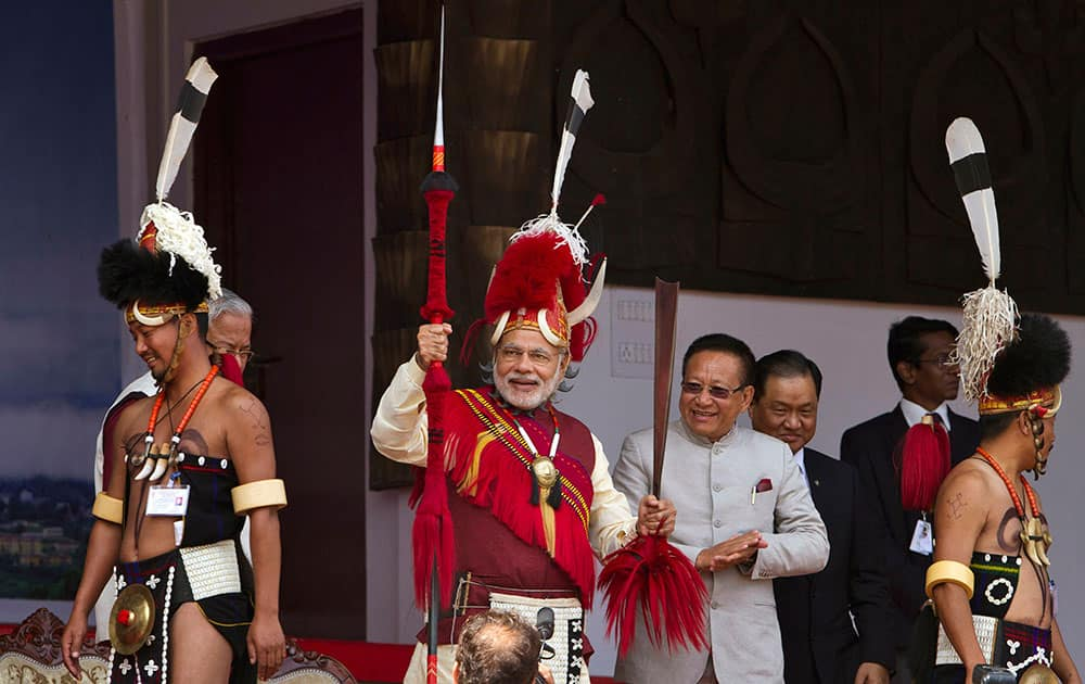 Indian Prime Minister Narendra Modi, center, in traditional attire holds a Naga spear and a sword during the inaugural ceremony of the Hornbill Festival in Kisama village in Nagaland.
