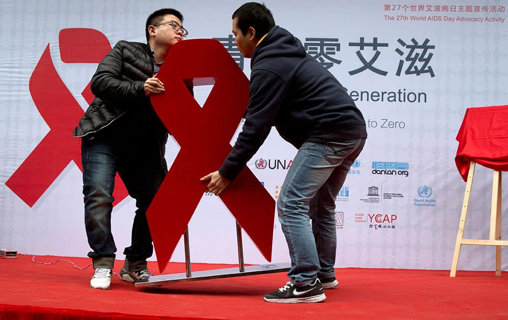 Chinese men move a red ribbon at an event to promote awareness of HIV testing ahead of the Dec. 1 World AIDS day in Beijing.
