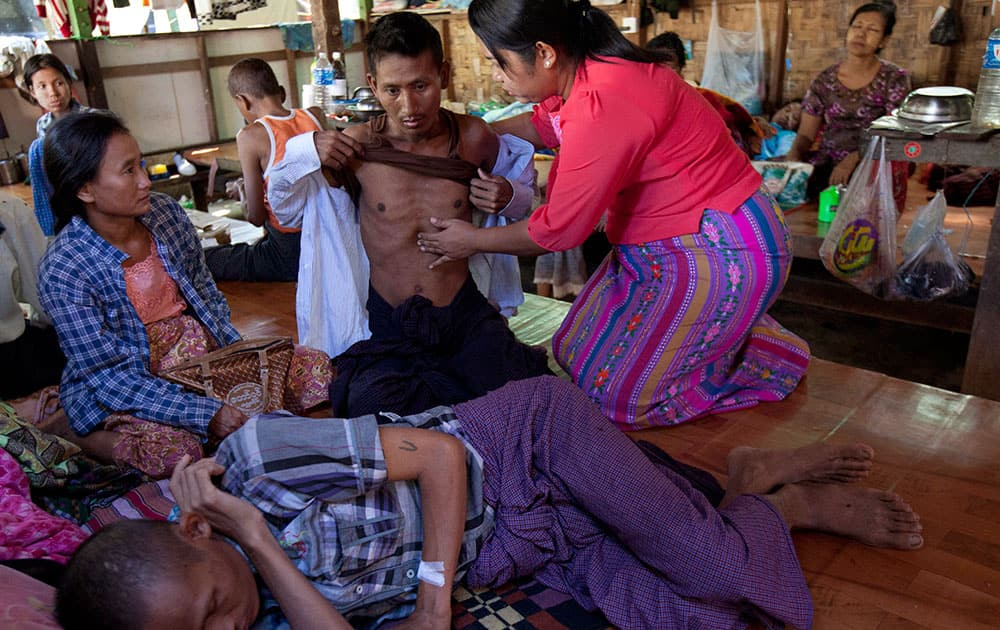 Phyu Phyu Thin, right, a parliament member of Myanmar Opposition Leader Aung San Suu Kyi's National League for Democracy party, examines an HIV patient while other patients rest at her HIV/AIDS Care Center in the outskirts of Yangon, Myanmar.