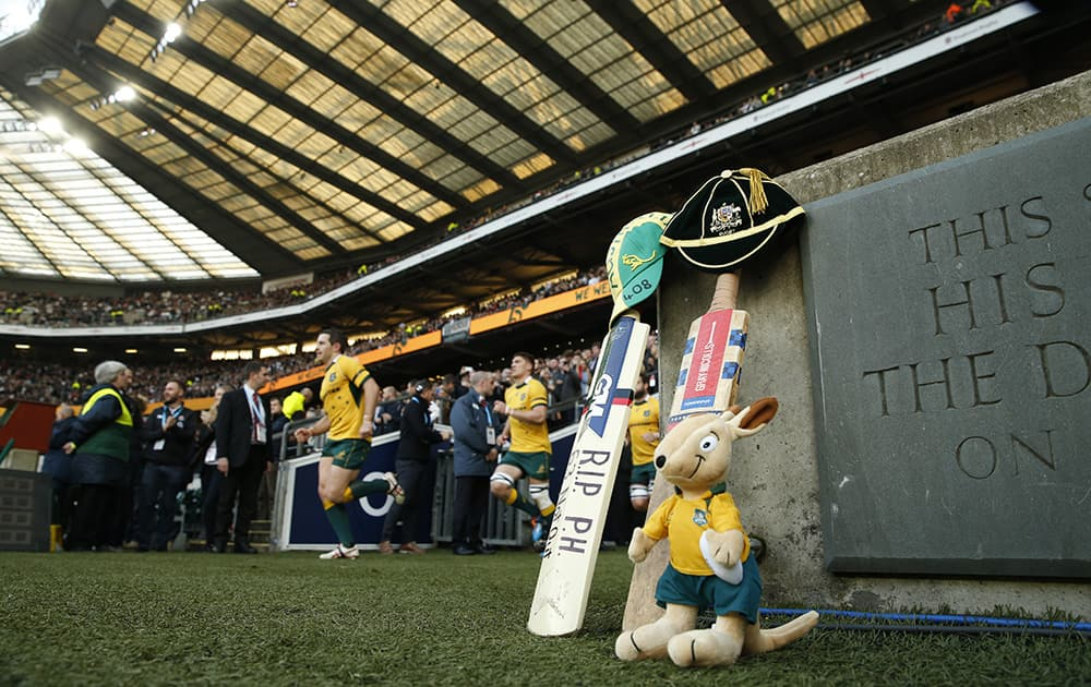 Members of the Australian rugby union team take to the pitch with cricket bats, Australian caps and a mascot are placed on the side of the pitch as a mark of respect to Australian cricketer Phil Hughes who died earlier this week, after being hit by a ball in a match at the Sydney Cricket Ground, prior to the international rugby union match between England and Australia at Twickenham stadium in London.