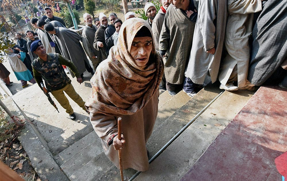 An elderly women entering a polling station to cast her vote for Assembly elections in Handwara district of Jammu and Kashmir on Tuesday. 18 assembly segments went to polling in the second phase of elections in the state.