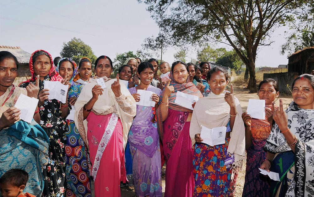 Voters show their ID cards and inked fingers after casting their votes for assembly elections outside a polling station at Karra, Khunti near Ranchi.