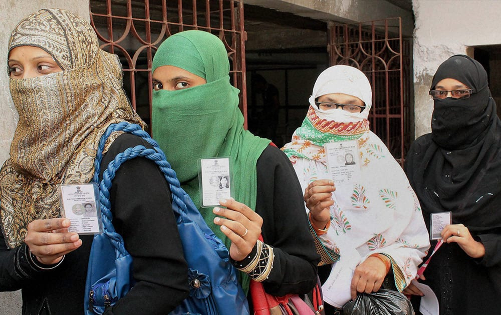 Muslim women exhibit their identity cards as they wait to cast their votes for the assembly elections at a polling station in Jamshedpur.