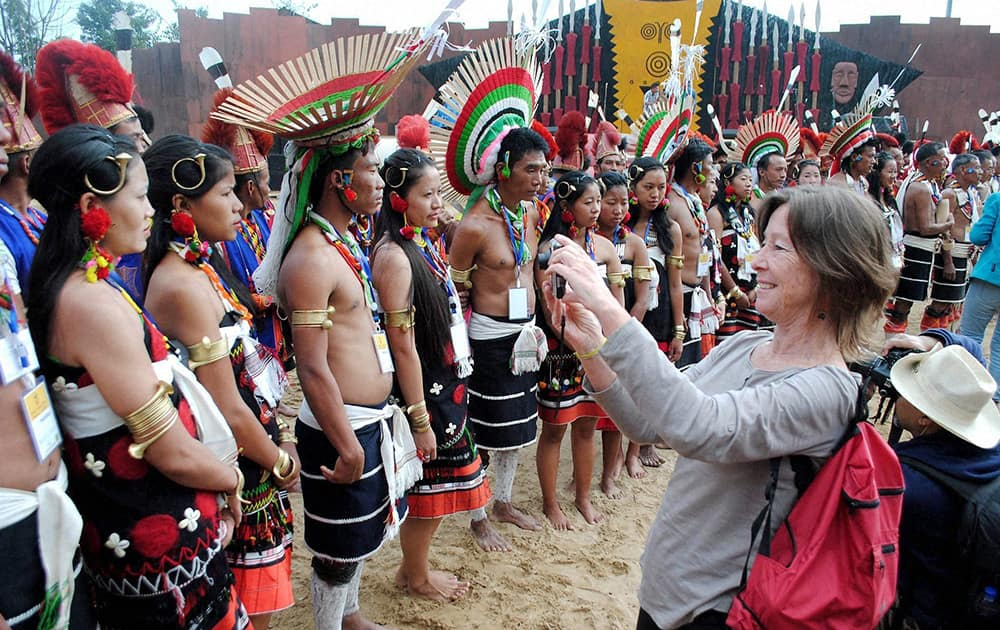 A foreign tourist taking photographs of different tribes of Nagaland during the 2nd day of Hornbill festival at Kisama village on the outskirts of Kohima in Nagaland.