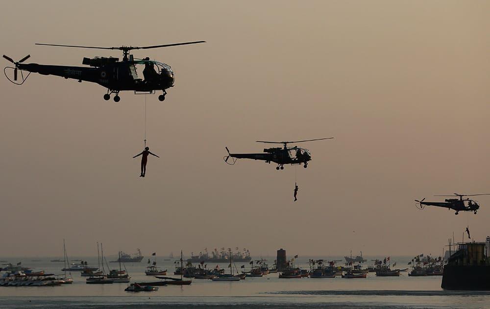Indian Navy Commando perform skills during Naval Day celebrations at the Arabian Sea in Mumbai.