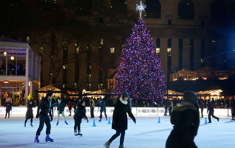 Skaters glide around the ice rink immediately after a Christmas tree lighting ceremony at Winter Village at Bryant Park, in New York.