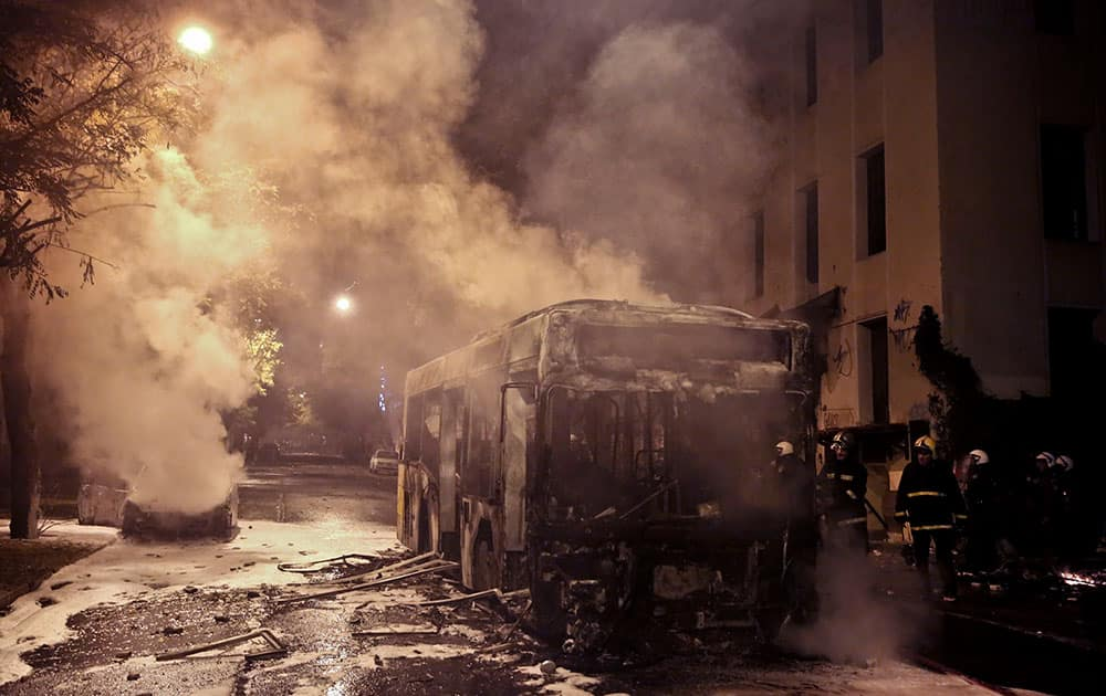 Firemen try to extinguish a bus and a car during clashes between anarchists and police in central Athens.