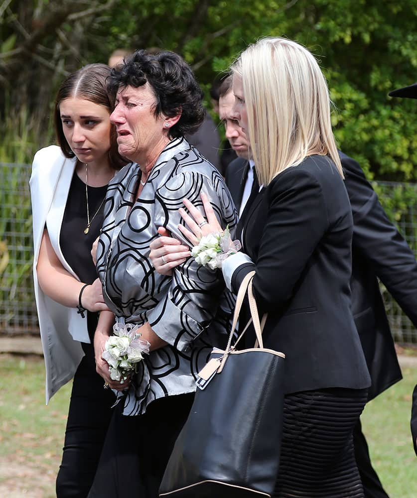Virginia Hughes, center, mother of Australian cricketer Phillip Hughes, is supported by mourners as they walk behind her son's coffin during his funeral in Macksville, Australia.