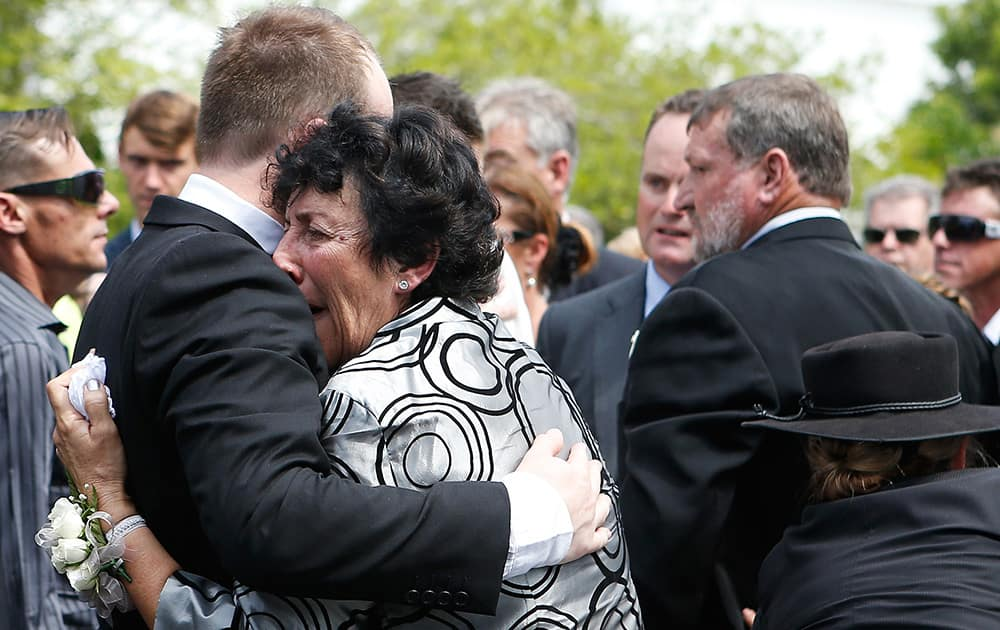 Virgina Hughes is comforted by her son, Jason, following the funeral of her other son Phillip in Macksville, Australia.