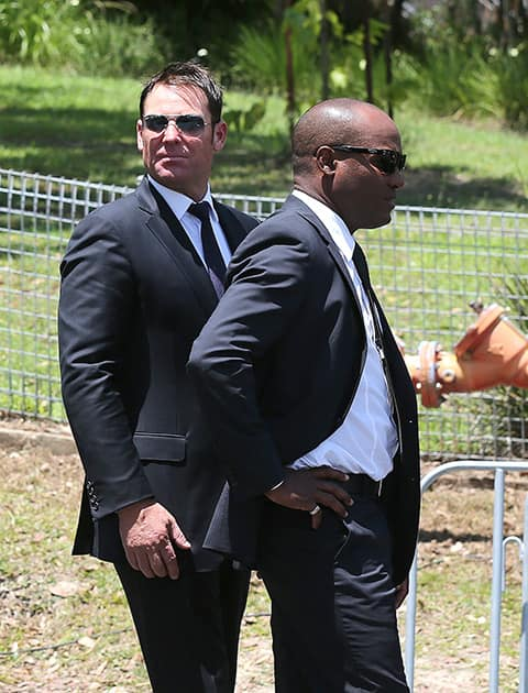 Former Australian cricketer Shane Warne and West Indies cricketer Brian Lara arrives for the funeral of Australian cricketer Phil Hughes in Macksville, Australia.