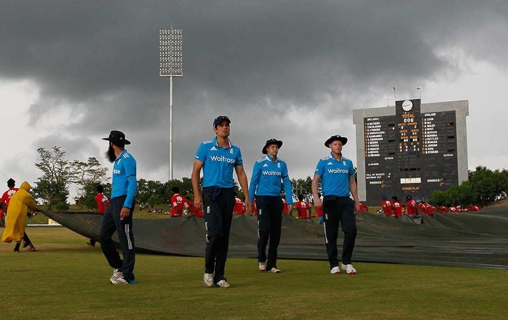 England's cricket team members walk off the field after play was stop due to bad light, as rain clouds hover over the stadium during the third one day international cricket match between Sri Lanka and England in Hambantota, Sri Lanka.