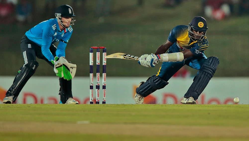 England's wicketkeeper Jos Buttler watches as Sri Lanka's Angelo Mathews plays a shot during the third one day international cricket match between them in Hambantota, Sri Lanka.
