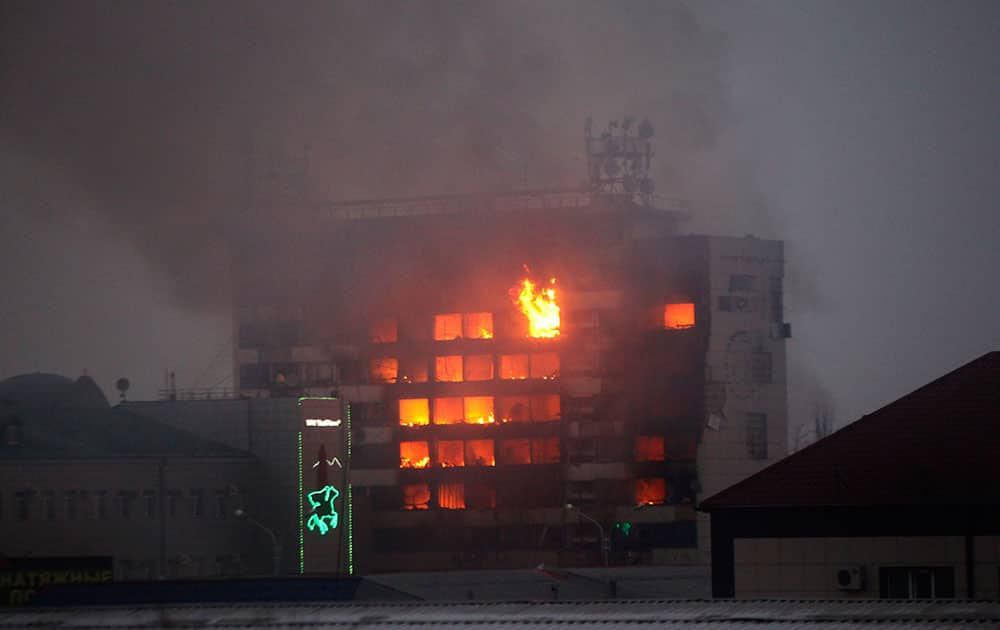 A publishing house building is seen in flames in the center of Grozny, Russia. A gun battle broke out after midnight Thursday in the capital of Russia's North Caucasus republic of Chechnya, puncturing the patina of stability ensured by years of heavy-handed rule by a Kremlin-appointed leader. Security officials and the leader of Chechnya said gunmen traveling in several cars killed at least three traffic police officers at a checkpoint late at night in the capital of the republic, Grozny.