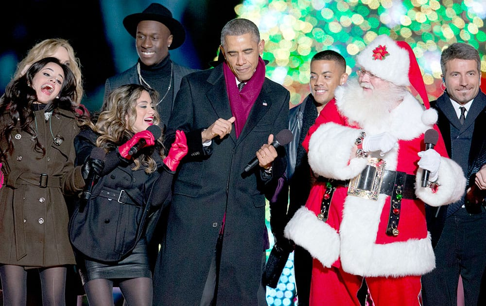 President Barack Obama dances on stage with Santa, members of Fifth Harmony, Nico & Vinz and The Tenors, behind, during the National Christmas Tree lighting ceremony at the Ellipse near the White House in Washington.