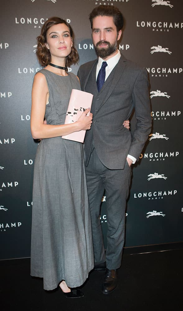 British model Alexa Chung and Jack Guinness pose at the opening of the Longchamp store in Paris, France.