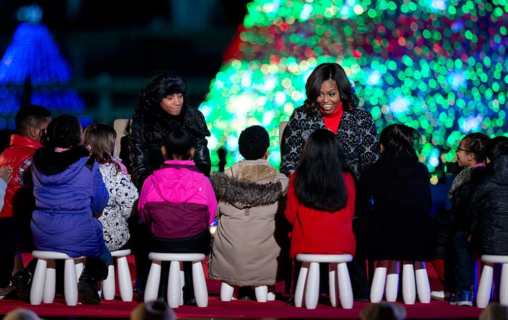First lady Michelle Obama, right, and little league pitcher Mo'ne Davis read 'Twas The Night Before Christmas' during the National Christmas Tree lighting ceremony at the Ellipse near the White House in Washington.