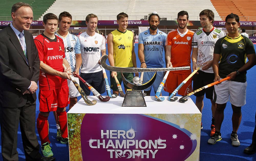 Captains of Hero Hockey Champions Trophy 2014 participating teams, pose for photographs near the champions trophy during its unveiling ceremony at Kalinga stadium in the eastern Indian city of Bhubaneswar.