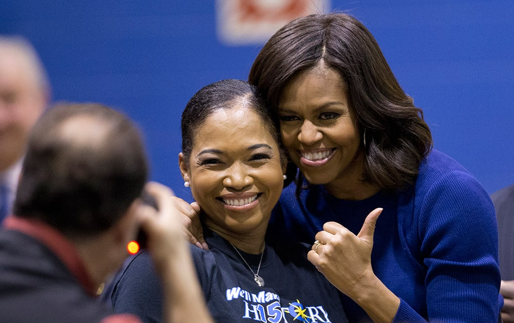 First lady Michelle Obama poses for a photo with Capital City Public Charter School's director college counseling Bridget Jackson at the after speaking Capital City Public Charter School in Washington.