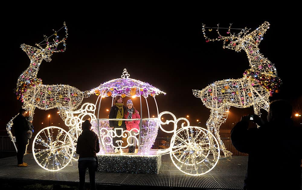 People have photos taken in a Christmas decoration on a street in Warsaw, Poland, as seasonal illuminations were switched on.