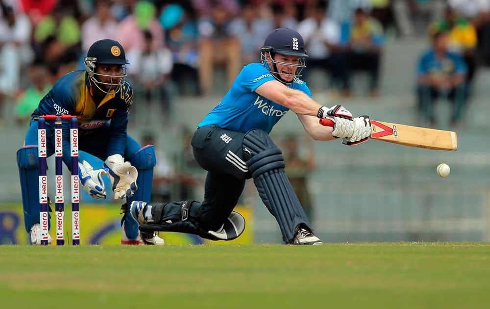 England's batsman Eoin Morgan plays a shot as Sri Lankan wicketkeeper Kumar Sangakkara watches during their fourth one day international cricket match in Colombo, Sri Lanka.