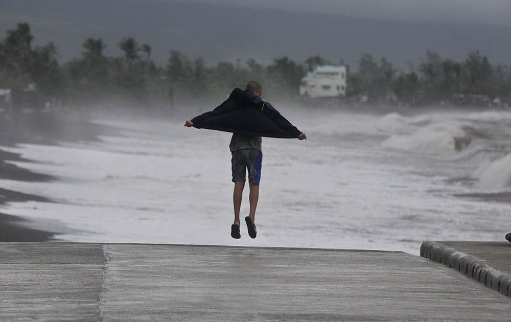 A resident jumps as he watches strong waves crash into shore as an effect of Typhoon Hagupit in Legazpi, Albay province, eastern Philippines.