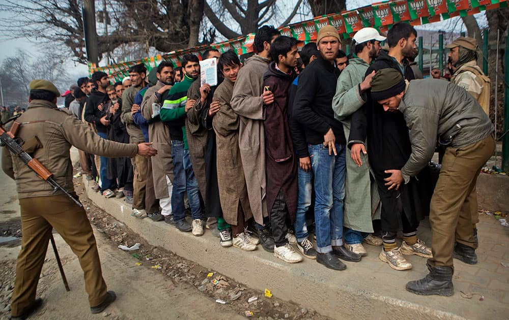 Indian policemen frisk the crowd outside Sheri Kashmir cricket stadium where Prime Minister Narendra Modi will address a campaign rally ahead of the local elections in Srinagar, India.