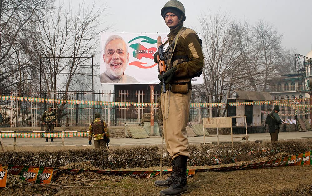 Indian paramilitary soldiers stand guard near Sheri Kashmir cricket stadium where Prime Minister Narendra Modi, portrait seen in the backdrop, is expected to address a campaign rally ahead of local elections in Srinagar, India.