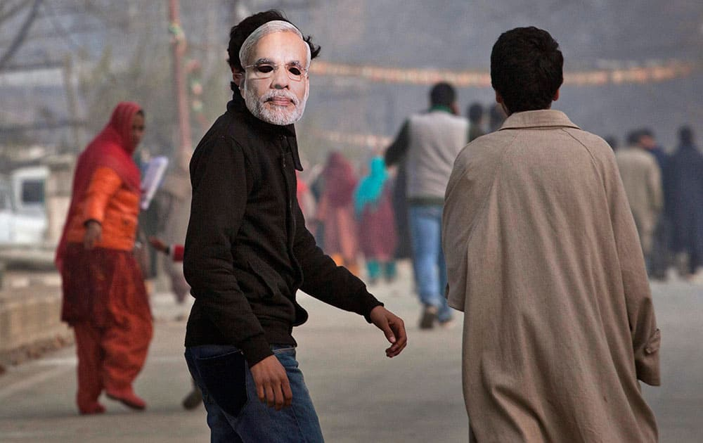 A Kashmiri boy wearing a mask of India's prime minister Narendra Modi walks towards the Sheri Kashmir cricket stadium to attend a campaign rally by Modi ahead of the local elections in Srinagar, India.