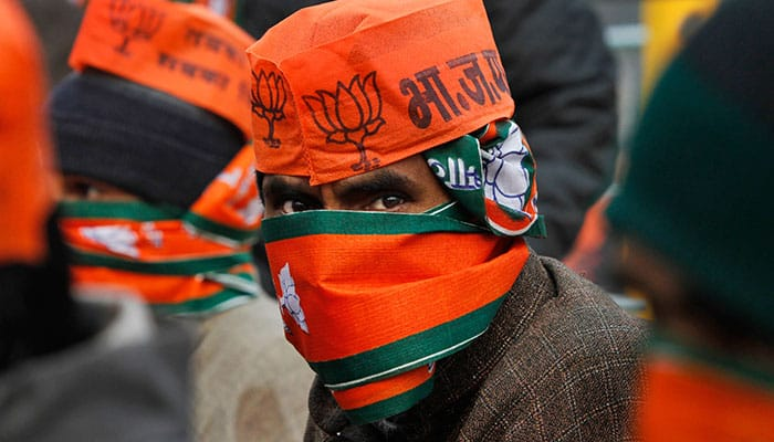 A Kashmiri supporter of Indian Prime Minister Narendra Modi, looks at camera as he and others await Modi's arrival during a campaign rally ahead of local elections in Srinagar.