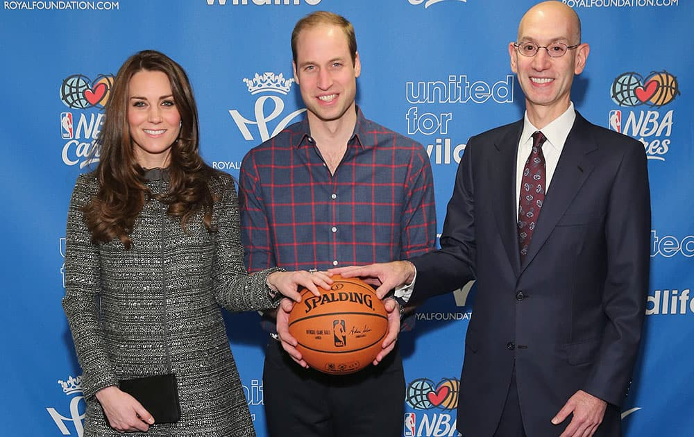 Britain's Prince William, the Duke of Cambridge, center, and Kate, the Duchess of Cambridge, left, pose for a photo with NBA Commissioner Adam Silverwhile attending an NBA basketball game between the Cleveland Cavaliers and Brooklyn Nets, in New York.