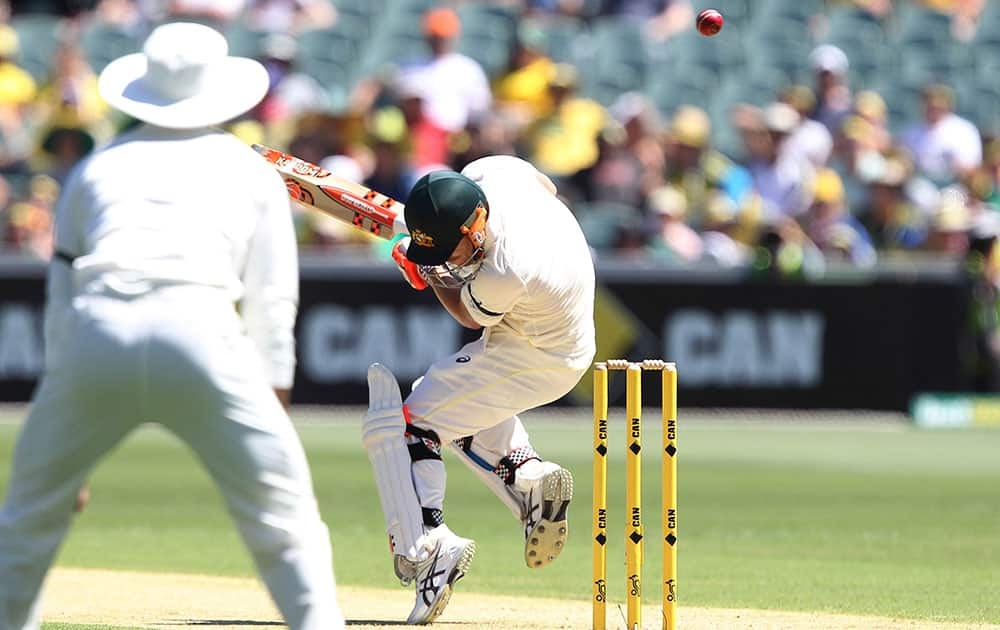 Australia's David Warner ducks a bouncer from India's Varun Aaron during Day 1 of the cricket match in Adelaide. Australia.