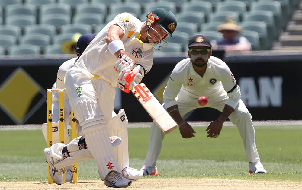 Australian batsman David Warner hits the ball during the first day of the first cricket test against India in Adelaide, Australia.
