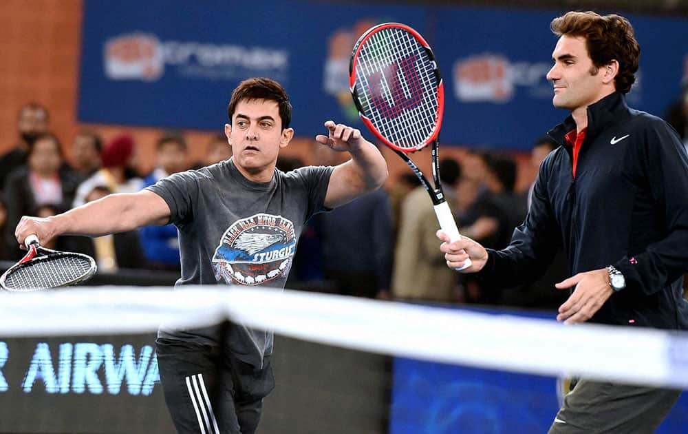 BOLLYWOOD ACTOR AAMIR KHAN PLAYS A SHOT AS TENNIS STAR ROGER FEDERER LOOKS ON DURING THE IPTL IN NEW DELHI.