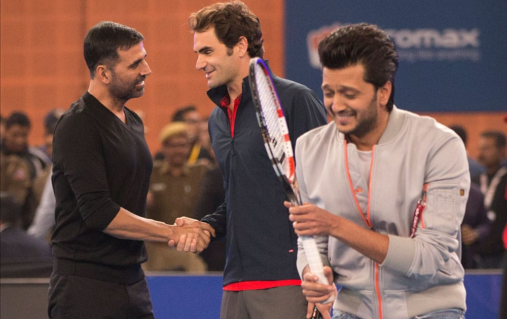 Micromax Indian Aces player Roger Federer, shakes hands with Indian Bollywood actor Akshay Kumar, left, as actor Ritesh Deshmukh passes by during a match on the sidelines of the International Premier Tennis League, in New Delhi.