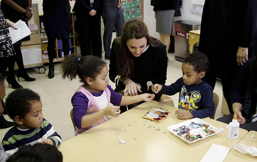 Kate, the Duchess of Cambridge, sits next to four-year-olds April, left, and Sammy in a pre-school class at the Northside Center for Childhood Development, in New York.