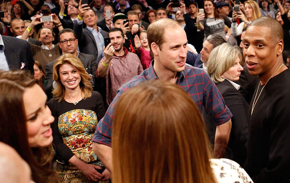 Britain's Prince William, second from right, talks with rapper and entrepreneur Jay-Z , far right, as Kate, left, the Duchess of Cambridge, chats with Jay Z's wife, entertainer Beyonce, foreground center, during an NBA basketball game between the Cleveland Cavaliers and the Brooklyn Nets at the Barclays Center in New York.