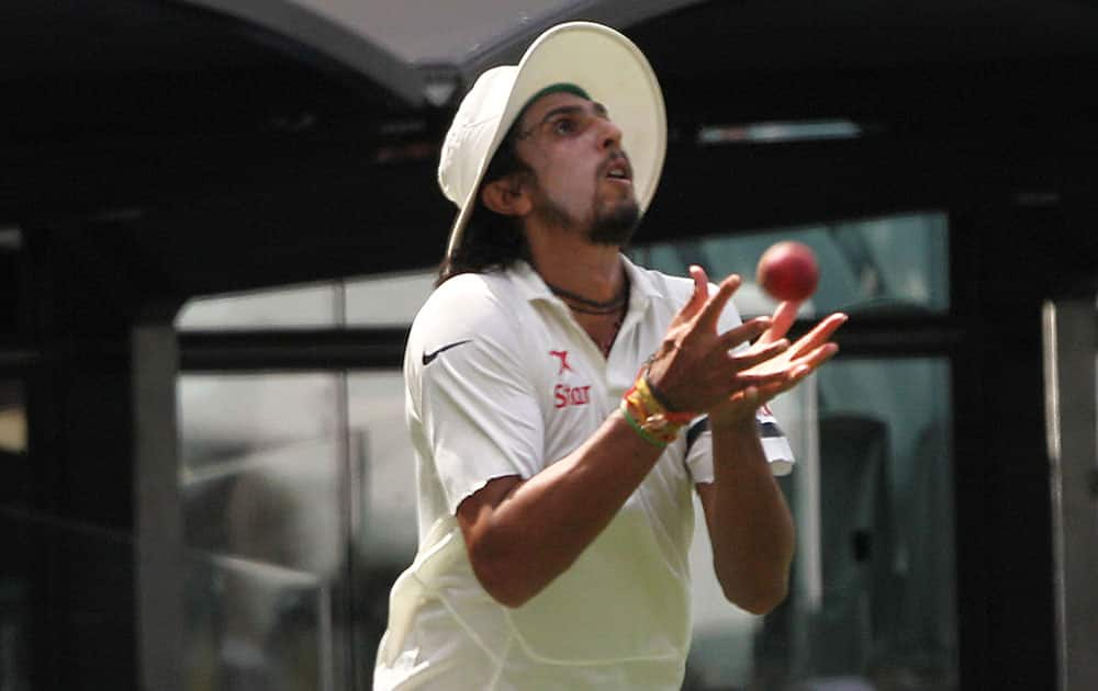 India's Ishant Sharma catches out Australia's David Warner during the first day of a cricket test match in Adelaide, Australia.