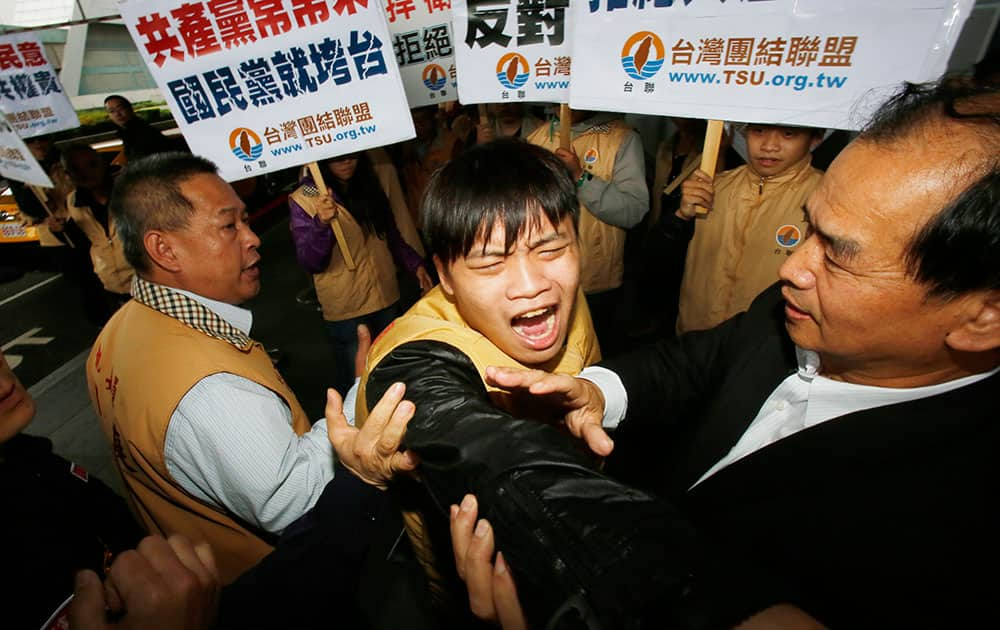 Opposition party supporters scuffle with police as they protest the arrival of Chen Deming, President of the Association for Relations Across the Taiwan Straits (ARATS), upon his arrival at the Taoyuan International Airport in Taoyuan, Taiwan.