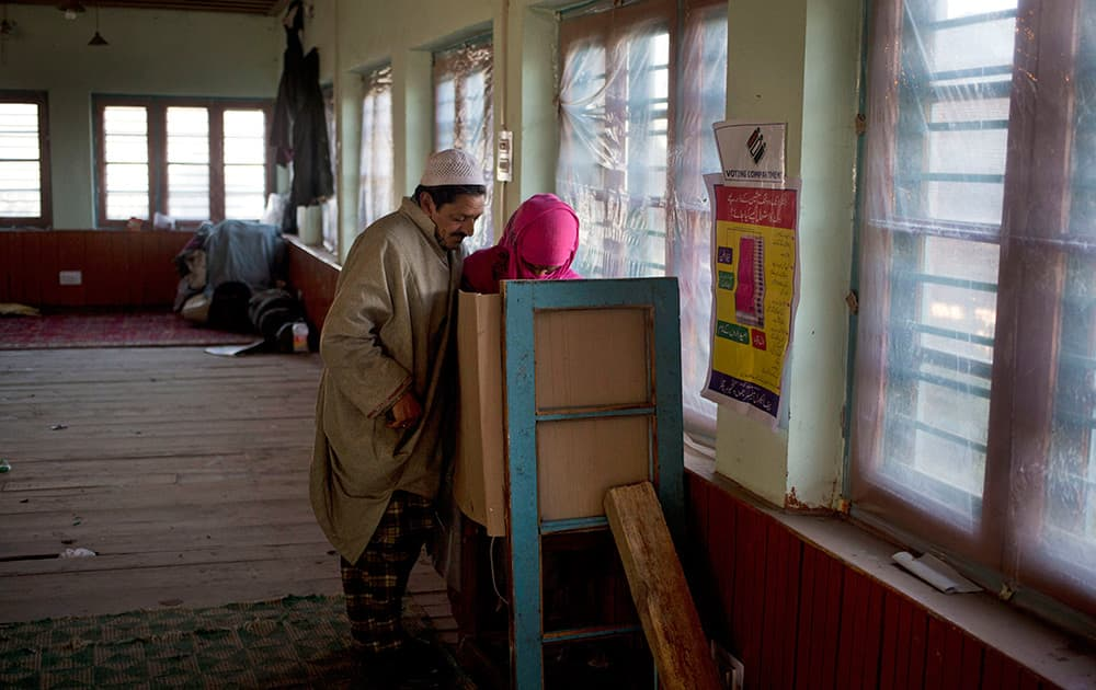 Ghulam Mohammad Dar, a Kashmiri man helps her sick wife Parveena Dar, as they cast their votes during the third phase polling of the Jammu and Kashmir state elections in Charar Sharief, about 40 kilometers (25 miles) south west of Srinagar, Kashmir.