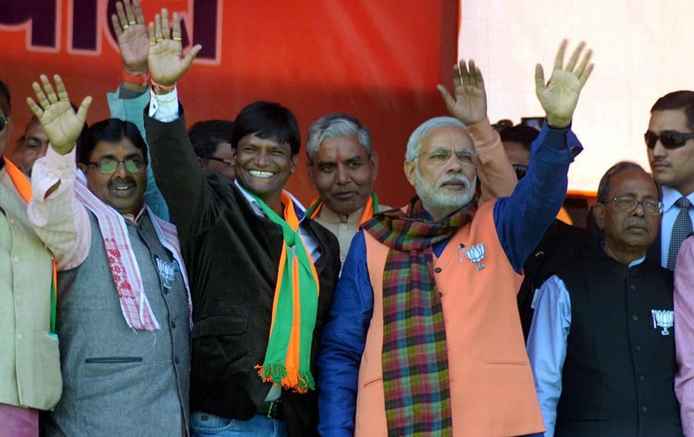 Prime Minister Narendra Modi waves to crowd at an election rally in support of NDA candidates in Dhandbad.