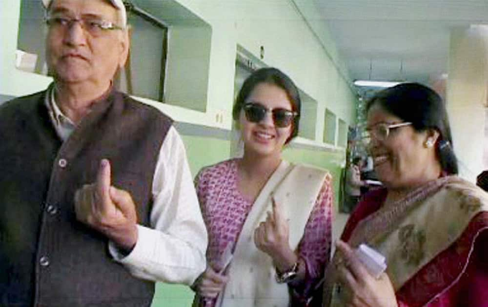 Mahendra Singh Dhonis father Paan Singh, mother and wife Sakshi Dhoni show their inked finger after casting their votes at a polling station in Ranchi.