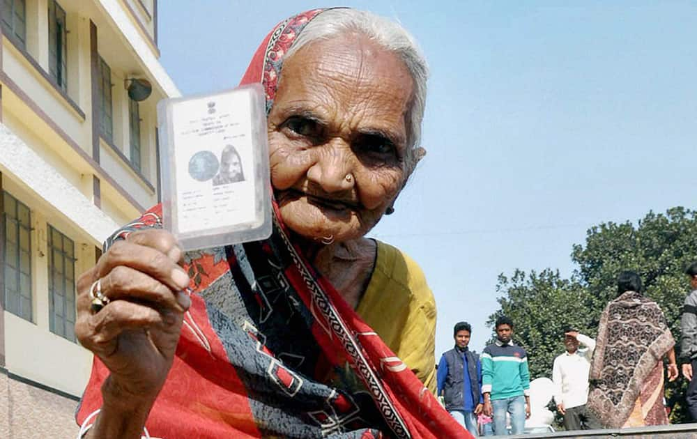 An elderly woman shows her voter card as she emerges out from the booth after casting her vote in the 3rd phase of the Jharkhand Assembly elections in the Ranchi.
