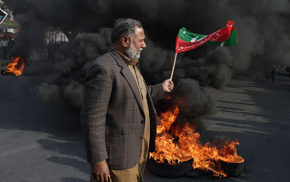 A supporter of Imran Khan's Pakistan Tehrik-e-Insaf party holds a party flag during a protest in Lahore, Pakstan.