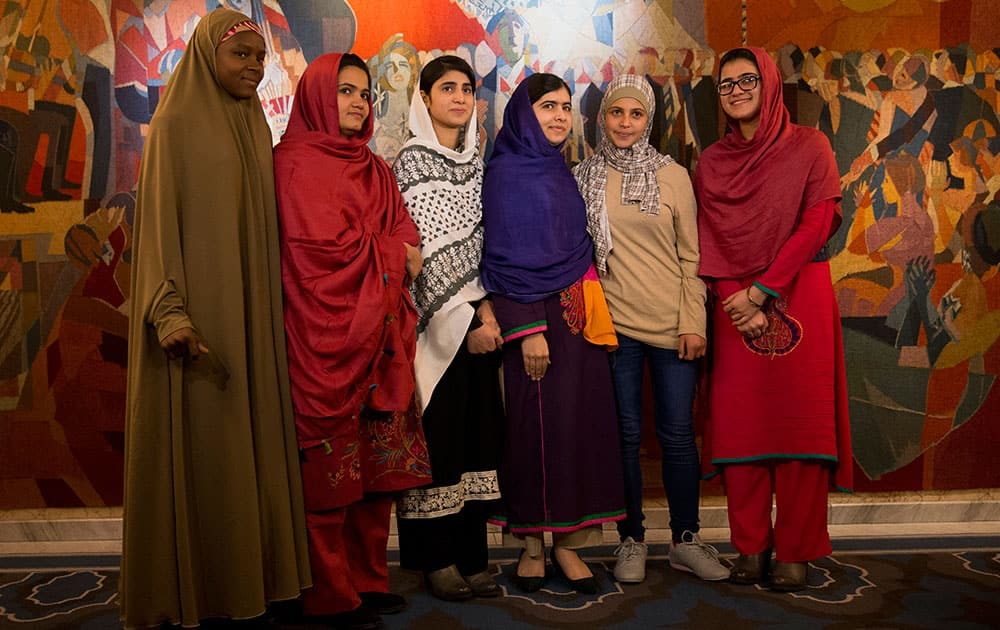 Joint Nobel Peace prize winner Malala Yousafzai, fourth left, stands with five young women she invited to attend the Nobel Peace Prize ceremony, from left, Nigeria's Amina Yusuf, Pakistan's Kainat Soomro, school friend Shazia Ramzan, Syria's Mezon Almellehan and school friend Kainat Riaz, as they pose for a group photograph before speaking to the media at Malala's hotel in Oslo, Norway.