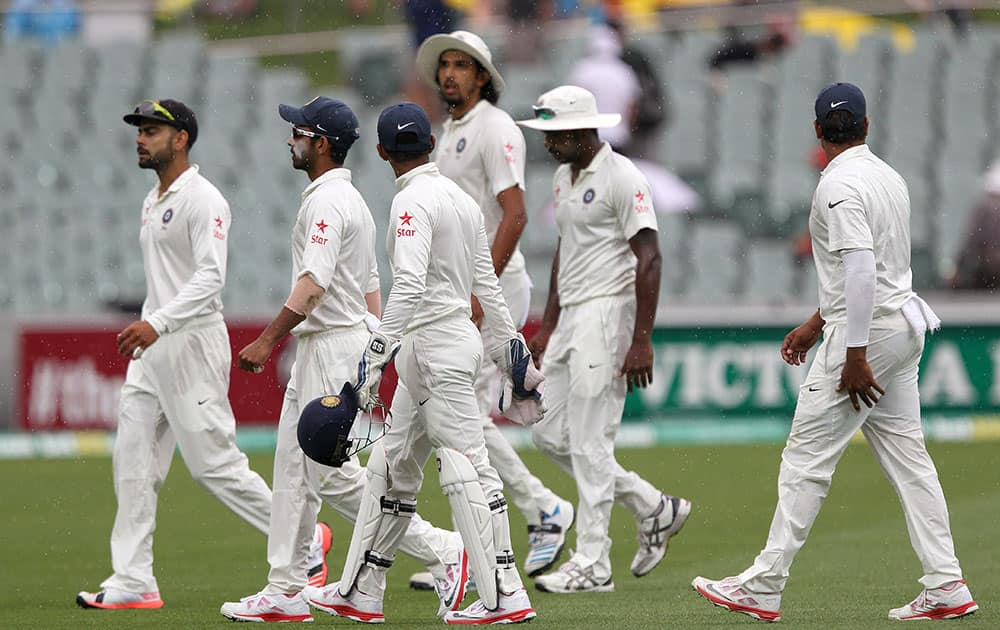 India players leave the field during a rain delay during the second day of their cricket test match against Australia in Adelaide, Australia.